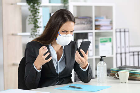 Angry executive woman looking smart phone avoiding covid-19 with mask sitting on a desk at office Stock Photo