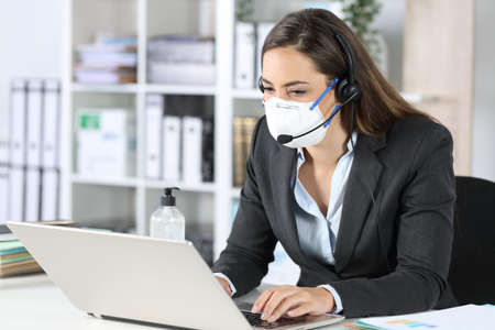 Telemarketer woman working on laptop avoiding covid-19 with mask sitting on a desk at office