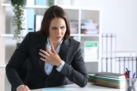 Ill executive woman suffocating and wheezing holding chest sitting at night in the office Banque d'images