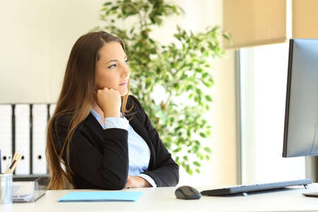 Serious office worker thinking looking away through a window