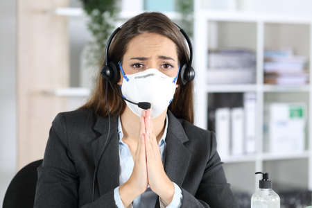 Front view of sad telemarketer woman avoiding covid-19 with mask begging looking camera sitting at the office