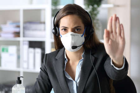 Serious telemarketer woman gesturing stop avoiding covid-19 with mask looking at camera sitting at the office