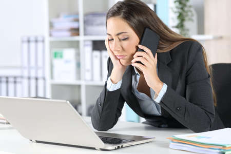 Bored executive calling on smart phone waiting on hold sitting on her desk at the office