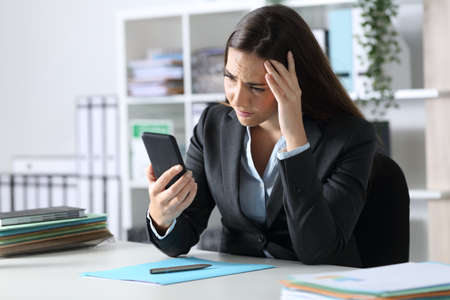 Sad executive woman reading bad news on smart phone sitting on a desk at office