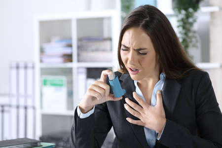 Executive woman holding inhaler with asthma attack suffocating sitting on a desk at office