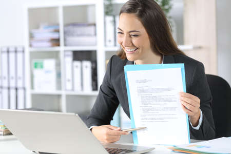 Happy executive woman pointing contract signature space on videocall on laptop sitting on her desk at office