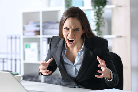 Angry executive woman looking at camera sitting on her desk at the office Archivio Fotografico