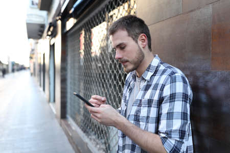 Side view portrait of a serious man using a smart phone in a street