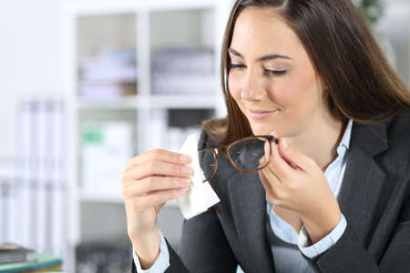 Happy executive woman with tissue paper cleaning eyeglasses sitting at the office