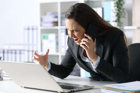 Angry executive woman calling on smart phone looking at laptop sitting on her desk at office Archivio Fotografico