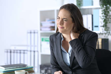 Executive woman with neckache complaining sitting on a desk at office
