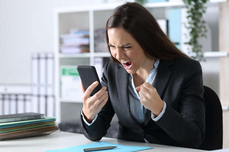 Angry executive woman reading bad news on smart phone sitting on a desk at office Archivio Fotografico