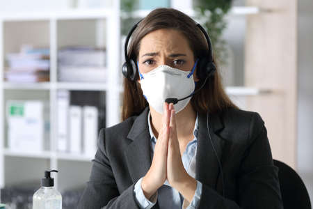 Sad telemarketer woman begging looking camera avoiding covid-19 with mask sitting at the office at night