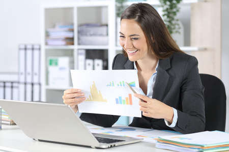 Happy executive woman shows good results in graph report on videocall on laptop sitting on her desk at office
