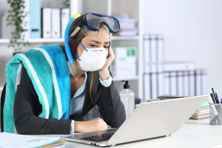 Sad executive wearing mask watching laptop at office with canceled vacation due coronavirus