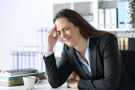 Executive in pain suffering headache touching head side sitting at office desk Archivio Fotografico