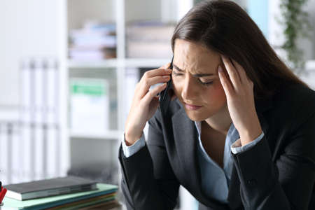 Sad executive woman calling on smart phone sitting at her office desk at night