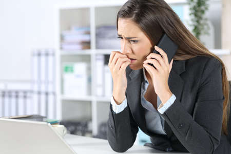 Nervous executive woman bitting nails calling on smart phone looking at laptop sitting on her desk at office