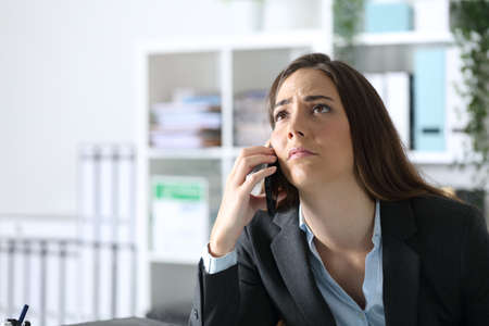 Impatient executive woman calling on smart phone looking up at the office