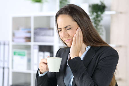 Executive woman in pain with toothache holding coffee cup sitting at the office Archivio Fotografico
