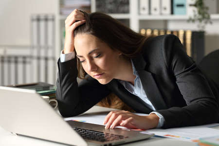 Overworked executive woman falling asleep sitting on her desk at night at office