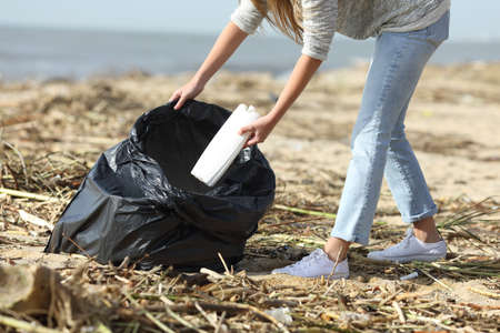 Close up of a volunteer cleaning a beach throwing plastic bottle into bag