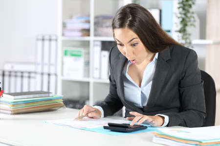 Amazed bookkeeper woman calculating on calculator ticking off document sitting on a desk at office Archivio Fotografico