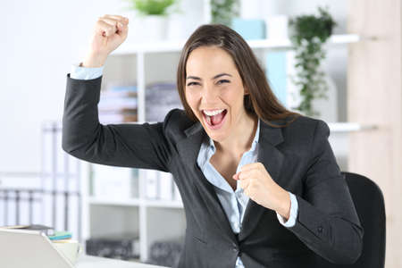 Excited executive woman celebrates good news looking at camera sitting on her desk at the office
