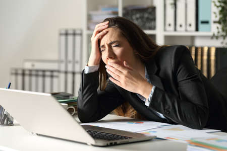 Tired executive woman yawning working late sitting on her desk at night at office