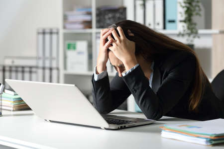 Sad executive woman with laptop complaining sitting on her desk at the office