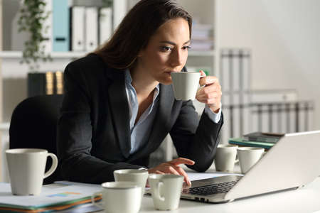 Executive woman overworking needing caffeine having several cups of coffee sitting on a desk at night at office
