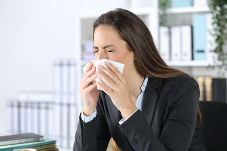 Executive woman sneezing using tissue paper covering mouth sitting on a desk at office Archivio Fotografico