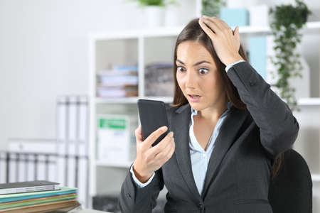 Surprised executive woman making mistake on smart phone sitting at office Archivio Fotografico