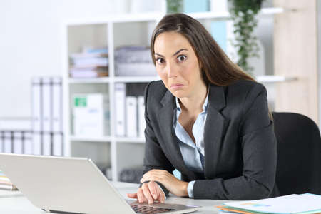 Confused executive woman with laptop looking at camera sitting on her desk at the office
