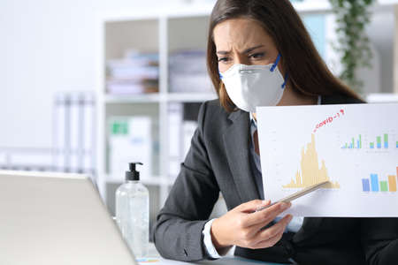 Worried executive woman wearing protective mask shows bad results report on videocall on laptop after covid-19 at the office Archivio Fotografico