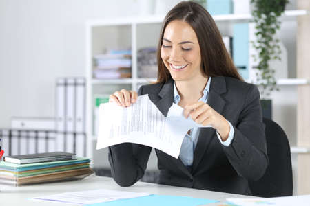 Happy executive woman breaking contract document sitting on a desk at office Archivio Fotografico