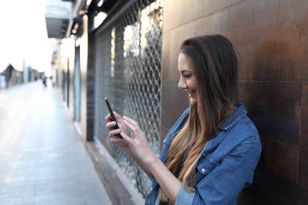 Side view portrait of a happy girl checks smart phone in the street