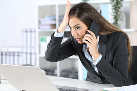 Surprised executive calling on smart phone discovers mistake on laptop sitting on her desk at the office