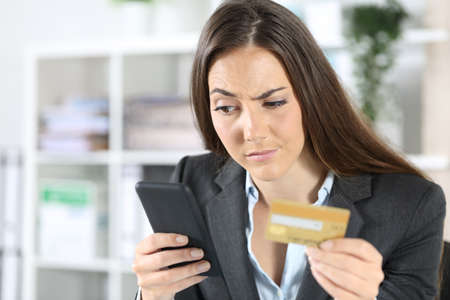 Suspicious executive woman pays with credit card on smart phone sitting at the office
