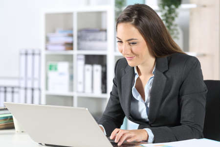 Happy executive woman working on laptop sitting on a desk at the office