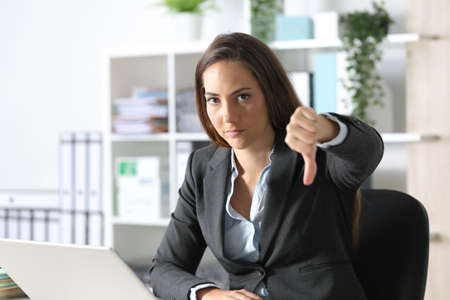 Serious executive woman gesturing thumbs down looking camera sitting on a desk at the office Archivio Fotografico