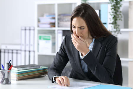 Tired overworked executive woman yawning sitting on a desk at the office