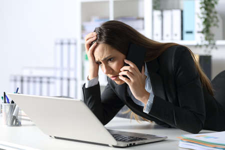Sad executive woman calling on smart phone reading on laptop sitting on her desk at office