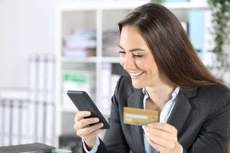 Happy executive woman paying online with credit card on smart phone sitting at the office