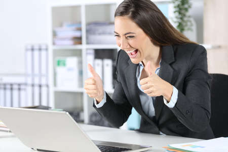 Happy executive woman with thumbs up on videocall on laptop sitting on her desk at office Archivio Fotografico