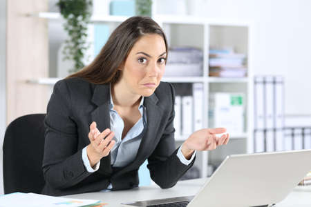 Confused businesswoman looking at camera with laptop sitting on her desk at office