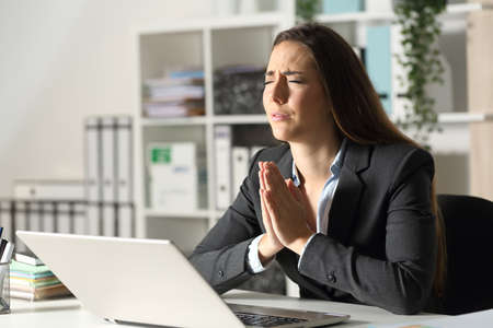 Worried executive woman with laptop praying sitting on her desk at night at office Stockfoto