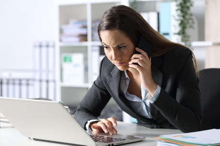 Suspicious executive woman calling on smart phone looking at laptop sitting on her desk at office Archivio Fotografico