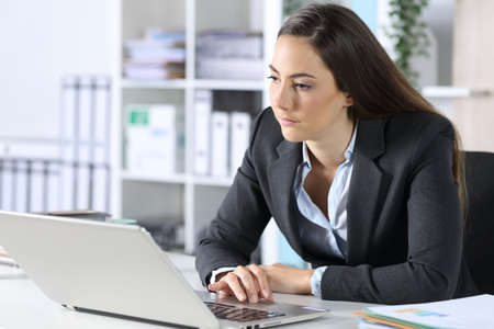 Distracted executive woman with laptop looking away sitting on her desk at the office