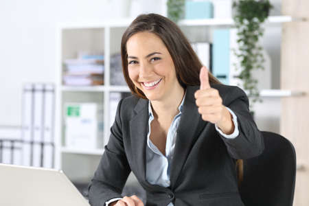 Happy executive woman gesturing thumbs up looking at camera sitting on a desk at the office Archivio Fotografico